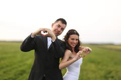Bride and groom making love sign - stock photo
