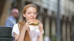 Quick lunch business woman. A young woman eating a hamburger on a city center. Stock Footage