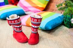 Red fur boots standing under green tree near color pillows, nobody, Christmas Stock Photos