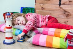 Young girl laying on the floor and playing toys, tired child Stock Photos