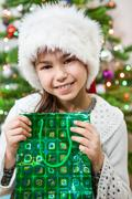Christmas portrait of young girl with green gift bag in hands - stock photo