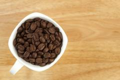 Coffee beans in a cup on wooden background Stock Photos