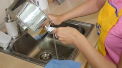 Beautiful woman washes pan in the kitchen sink Stock Footage