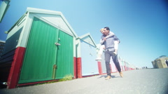 4K Couple playing piggyback pause for a selfie in front of colourful beach huts Stock Footage