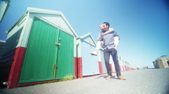 4K Couple playing piggyback pause for a selfie in front of colourful beach huts - stock footage