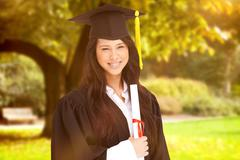 Composite image of a woman standing to the side slightly with her degree and - stock photo