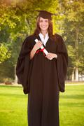 Stock Photo of Composite image of full length shot of a graduate holding a degree and looking