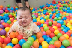 Crying Baby Girl in Ball Pit - stock photo
