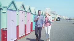 4K Happy romantic couple eating ice cream as they walk past colourful beach huts Stock Footage