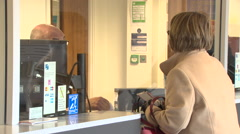 Woman at ticket counter of train station Stock Footage
