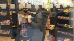 Woman in a newsagents looking at magazines Stock Footage