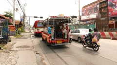 Baht bus with passengers slowly drive along busy road, follow camera Stock Footage