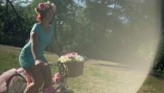 young woman rides a bicycle decorated with flowers in the park slow motion - stock footage