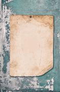 old paper on cracked  concrete wall - stock photo