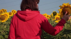 Woman in sunflower field, checking, looking, plants, crop Stock Footage