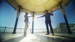 4K Attractive couple having fun together, dancing in bandstand in summer Stock Footage