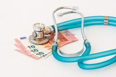 Expensive health treatment.  Stethoscope on money background - stock photo