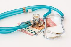 Stock Photo of Expensive health treatment.  Stethoscope on money background