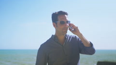 4K Portrait of attractive smiling man with mobile phone at the beach - stock footage
