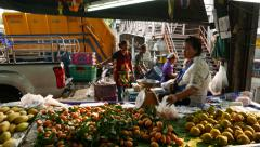 Seller woman seat at marian plum fruit stall, rear side view, then go away Stock Footage
