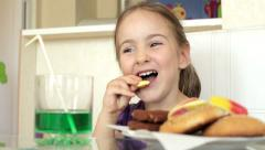 Smiling little girl eating cookie or biscuit, Model Release - stock footage