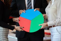 Business team assembling a chart to represent finance Stock Photos