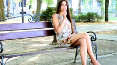 Cute girl sucking a candy on a stick on the bench Stock Footage
