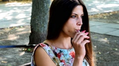 Beautiful girl eating a candy on a stick in the Park - stock footage