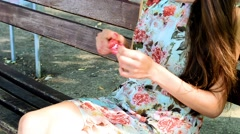 Beautiful girl takes off the wrapper from the candy on a stick - stock footage