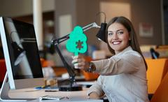 Business woman sitting in the office and holding puzzle with peace missing Stock Photos