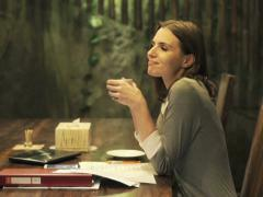 Pretty businesswoman relaxing with coffee sitting by table at home at night NTSC Stock Footage