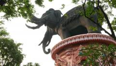 Rear-side tilt shot of giant three-headed elephant sculpture, seen through trees - stock footage