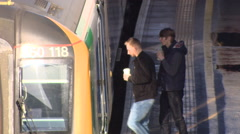 high angle shot of commuters getting onto train - stock footage