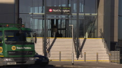 Mid shot of traffic past a train station in Northampton Stock Footage
