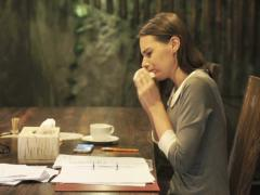 Pretty businesswoman with a cold sitting by table at home at night NTSC Stock Footage