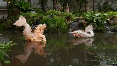 Grotesque fish sculptures over small pond water, Himmapan garden - stock footage