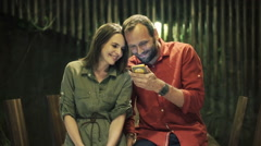 Happy, young couple watching movie on smartphone at home at night  HD Stock Footage