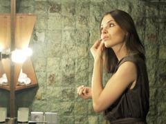 Woman applying makeup, powder on her face in the bathroom at night NTSC - stock footage
