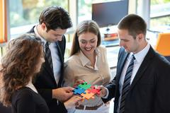 Business people assembling jigsaw puzzle - stock photo