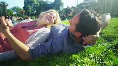 4K Attractive romantic couple kissing and laughing as they relax in a park. Stock Footage