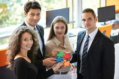 Business people assembling jigsaw puzzle to represent teamwork - stock photo