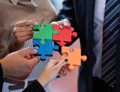 Business people assembling jigsaw puzzle to represent teamwork Stock Photos