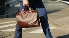 Businessman with leather bag walking down the street Stock Footage