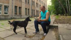 A man rests in the old park after the race. Feeding stray dogs Stock Footage