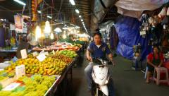 Full stalls of fruits, man sits motorcycle show fingers on camera, glide shot Stock Footage