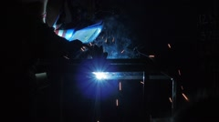 Industrial worker welding metal in slow motion with hot sparks floating around. Stock Footage