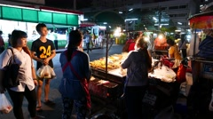 Mobile kitchen, street food on sticks, night alley near market, people waiting Stock Footage