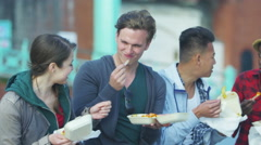 4k Happy mixed ethnicity group of friends eating fried chips in urban area Stock Footage