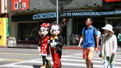 4K, Mickey Mouse and Toddler Minnie mouse on Hollywood Boulevard in Los Angeles Stock Footage