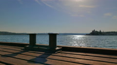 Early morning. Pier and bollard in the sunlight. - stock footage
